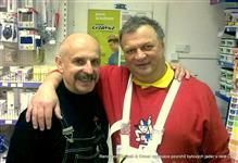 Karel Koubek a Miroslav Koubek v nových montérkách černé a bílé se drží kolem ramen v prodejně na školení a s úsměvem