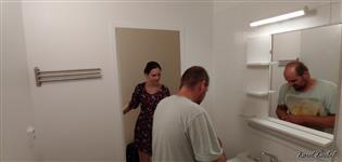 A již jen přišroubovat do koupelny bytového umakartového jádra doplňky a je hotovo. Renovátor Vlastimil Kraus u zrcadlové poličky v koupelně a usměvavá slečna zákaznice jej pozoruje u vstupu do koupelny, děkujeme.