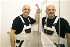 Renovace povrchů kopelny a toalety umakartového jádra bez bourání v bílé barvě předává Karel Koubek s úsměvem do zrcadlové toaletní skříňky držící se za sprchovou hlavici